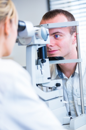 eye exam: Optometry concept - handsome young man having his eyes examined by an eye doctor (color toned image; shallow DOF)