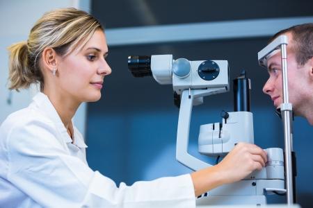 Optometrie-Konzept - hübsche junge Mann mit seinen Augen von einem Augenarzt (Farbe getönt Bild; shallow DOF)