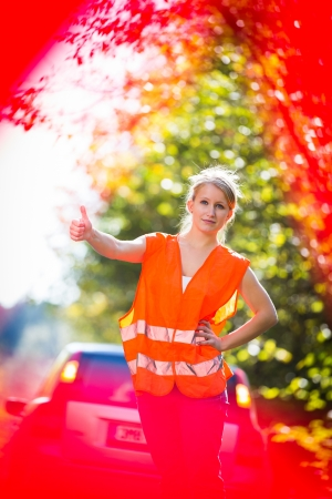 Young female driver wearing a high visibility vest on the roadside after her car has broken down Stock Photo - 18609551
