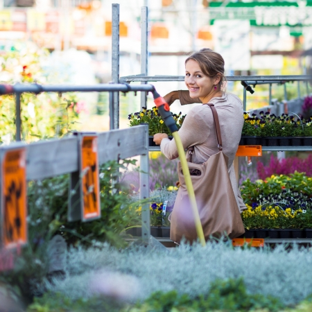Young woman buying flowers at a garden center (color toned image; shallow DOF) Imagens