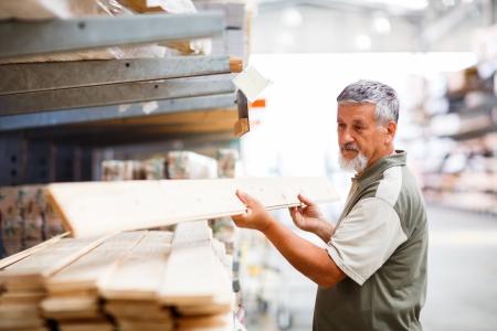 Älterer Mann, der Kauf Bau-Holz in einem Baumarkt