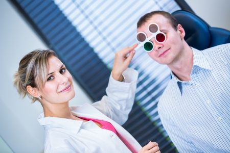 blind people: Optometry concept - handsome young man having his eyes examined by an eye doctor (color toned image; shallow DOF)