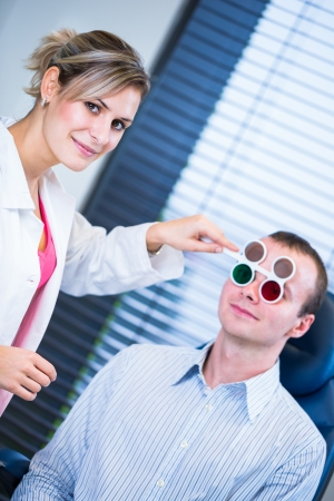medical examination: Optometry concept - handsome young man having his eyes examined by an eye doctor (color toned image; shallow DOF)