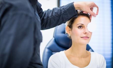 Optometrie-Konzept - hübsche junge Frau, die ihre Augen von einem Augenarzt  Optiker untersucht (Farbe getönt Bild; shallow DOF)