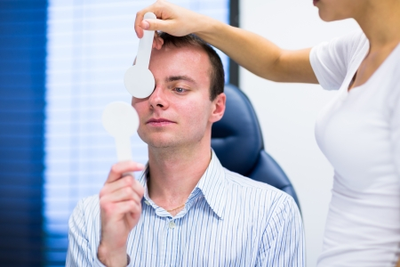 oculist: Optometry concept - handsome young man having his eyes examined by an eye doctor (color toned image; shallow DOF)