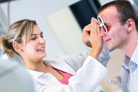 Optometry concept - handsome young man having his eyes examined by an eye doctor photo