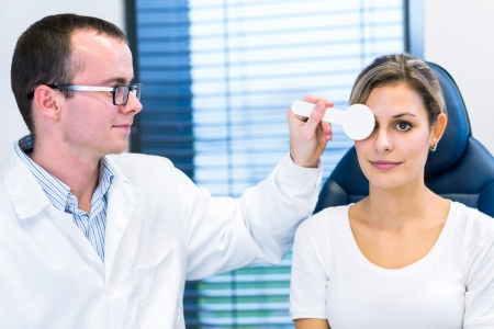 eye test: Optometry concept - pretty young woman having her eyes examined by an eye doctor