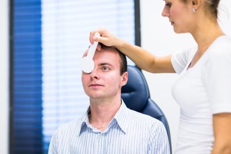 examen de la vista: Concepto de Optometría - apuesto joven que tenga a sus ojos sean examinados por un oftalmólogo