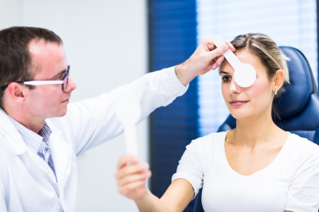 oculist: Optometry concept - pretty young woman having her eyes examined by an eye doctor