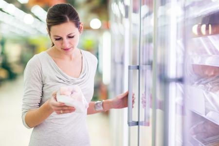 Junge Frau beim Einkaufen für Fleisch in einem Lebensmittelgeschäft (Farbe getönt Bild) Lizenzfreie Bilder