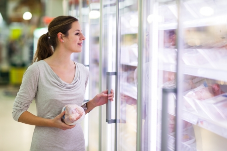 produce sections: Young woman shopping for meat in a grocery store