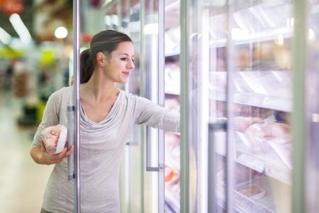 Junge Frau beim Einkaufen für Fleisch in einem Lebensmittelgeschäft