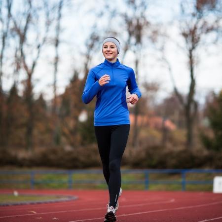 Junge Frau läuft bei einem track and field Stadion Lizenzfreie Bilder