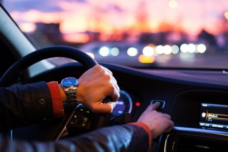 Autofahren bei Nacht-Mann fährt mit seinem modernen Auto in der Nacht in einer Stadt (shallow DOF, Farbe getönt Bild)