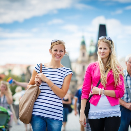 czech women: Two female tourists walking along the Charles Bridge while sightseeing in Prague, the historical capital of the Czech Republic