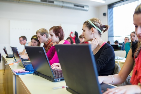 college classroom: College students sitting in a classroom, using laptop computers during class