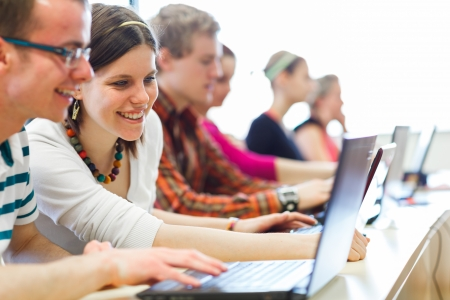 College-Studenten sitzen in einem Klassenzimmer mit Laptop-Computer während des Unterrichts Lizenzfreie Bilder