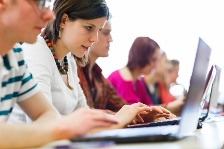 higher learning: College students sitting in a classroom, using laptop computers during class