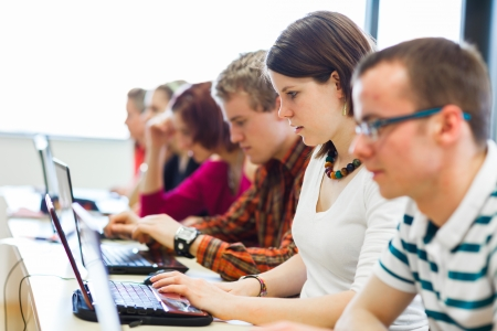 1 and group: College students sitting in a classroom, using laptop computers during class