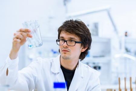 scientific equipment: Young male researcher carrying out scientific research in a lab  Stock Photo