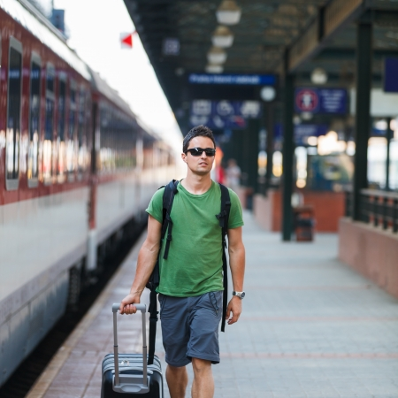 modern train: Just arrived: handsome young man walking along a platform at a modern train station