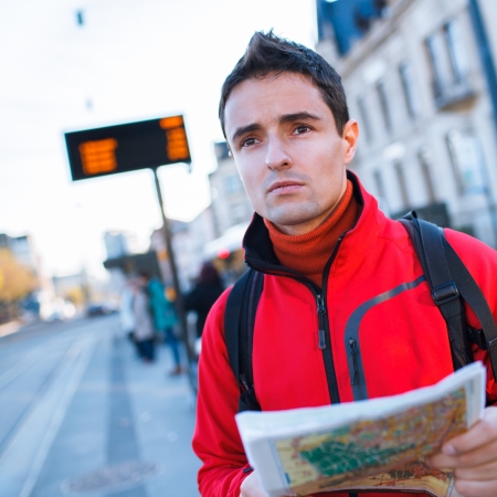 Just arrived: handsome young man studying a map on a bus stop in front of a train station photo