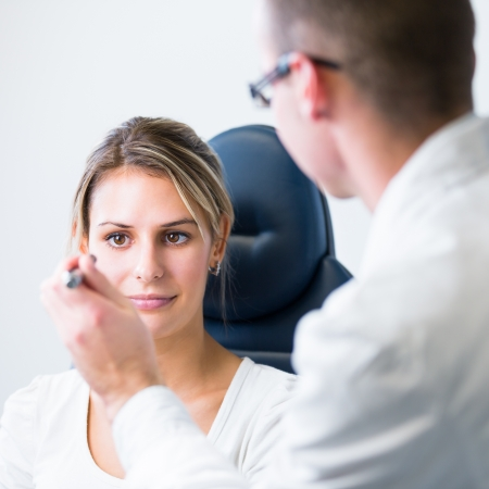 eye doctor: optometry concept - pretty young woman having her eyes examined by an eye doctor
