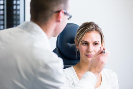 Optometrie-Konzept - hübsche junge Frau, die ihre Augen von einem Augenarzt (flache DOF, Farbe getönt Bild)