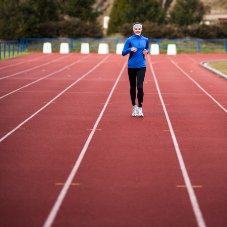 train tracks: Young woman running at a track and field stadium Stock Photo