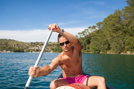 canoe paddle: Handsome young man on a canoe on a lake, paddling, enjoying a lovely summer day Stock Photo