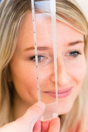examen de la vista: Concepto de Optometr?a - mujer bastante joven que hace sus ojos sean examinados por un oftalm?logo Foto de archivo