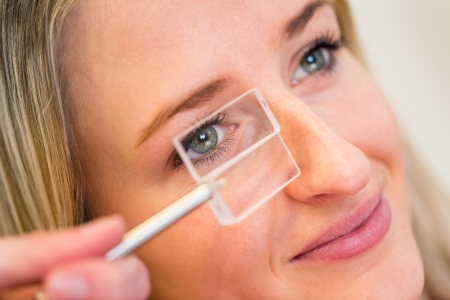 myopia: Optometry concept - pretty young woman having her eyes examined by an eye doctor