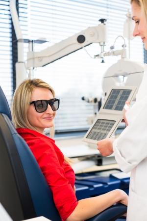 Optometrie-Konzept - hübsche junge Frau, die ihre Augen von einem Augenarzt (Farbe getönten Bild, shallow DOF)