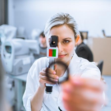 Concepto de Optometría - bastante joven optometrista en el trabajo, examinating tus ojos Foto de archivo