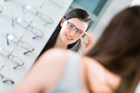 Pretty, young woman choosing new glasses frames in an optician store photo