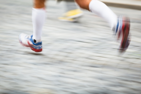 man legs: Motion blurred runners feet in a city environment - running marathon (panning technique used -> motion blurred image; color toned image) Stock Photo