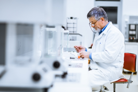 investigador cientifico: Investigador senior masculina llevar a cabo la investigación científica en un laboratorio