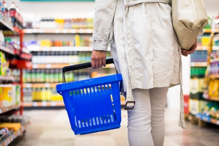 Hübsche junge Frau kauft Lebensmittel in einem Supermarkt Einkaufszentrum Lebensmittelgeschäft Farbe getönten Bild, shallow DOF