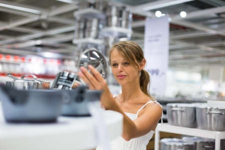 Pretty, young woman choosing a the right pot for her cooking in a modern home furnishings store  color toned image Stock Photo - 21461900