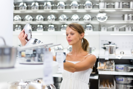 Pretty, young woman choosing a the right pot for her cooking in a modern home furnishings store  color toned image; shallow DOF Stock Photo - 21461940
