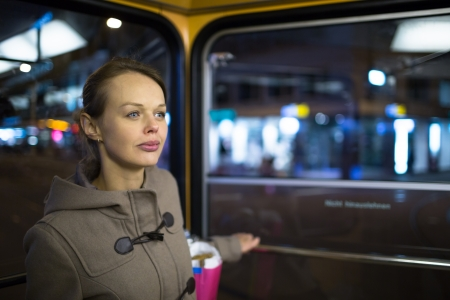 Pretty, young woman on a streetcar tramway, during her evening commute home from work  color toned image  photo