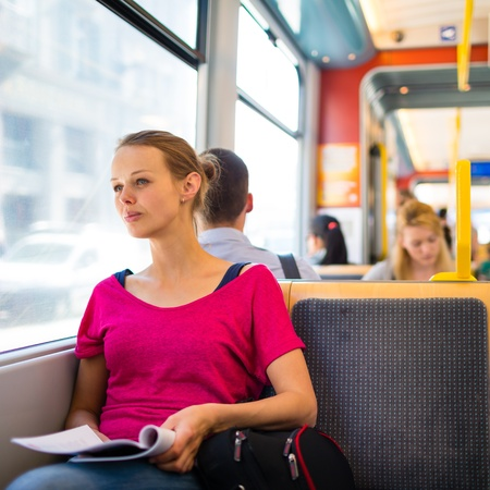 tramway: Pretty, young woman on a streetcar tramway, during her commute to work school  color toned image Stock Photo
