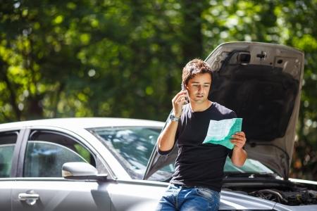 Knappe jonge man bellen voor hulp met zijn auto door de berm kapot