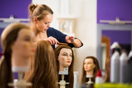 Pretty female hairdresser haidressing apprentice student training on an apprentice head photo