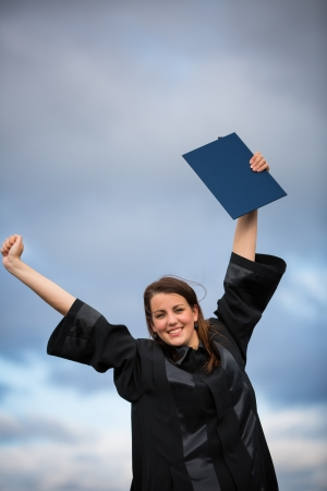 Pretty, young woman celebrating joyfully her graduation - spreading wide her arms, holding her diploma, savouring her success  color toned image; shallow DOF  photo