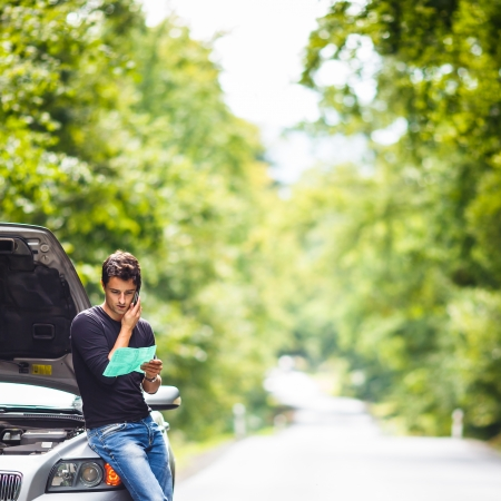 Handsome junge Mann ruft um Hilfe mit seinem Auto am Straßenrand nach unten gebrochen