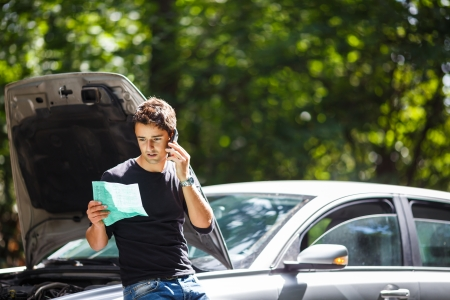 gass: Handsome young man calling for assistance with his car broken down by the roadside