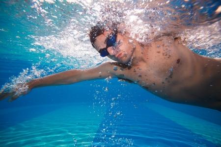 Junger Mann, die schwimmen Kraulen in einem Pool - Unterwasseraufnahme Farbe getönt Lizenzfreie Bilder
