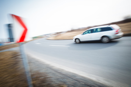 sharp curve: Traffic concept: car driving fast through a sharp turn (motion blur is used to convey movement)