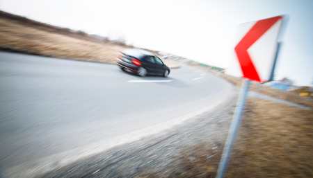 Traffic concept: car driving fast through a sharp turn (motion blur is used to convey movement) photo